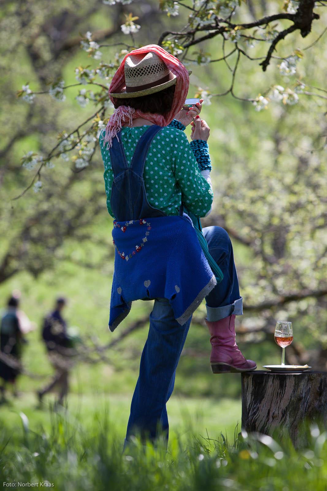 Künstlerin Dietlinde Elsässer in der Maske unter Kirschenblüten.